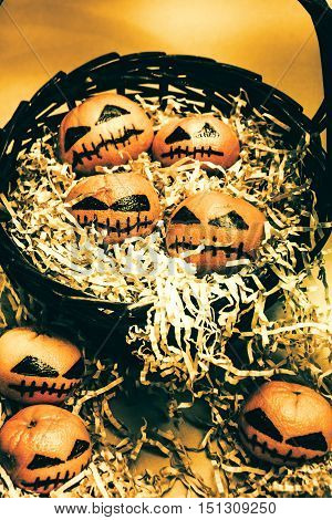 Basket of little halloween horrors with tiny evil pumpkin heads made from citrus fruits