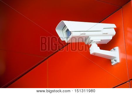 Security camera on the red wall. Private property protection