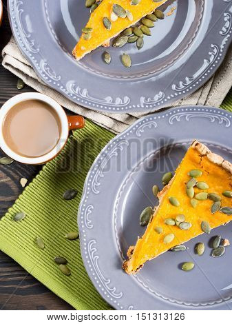 Slice of fall shortcrust pumpkin pie with pumpkin seeds on rustic wooden table with green napkin. Top view. Vertical image
