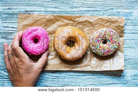 Colorful Donuts breakfast composition with different color styles of doughnuts over an aged wooden desk background.