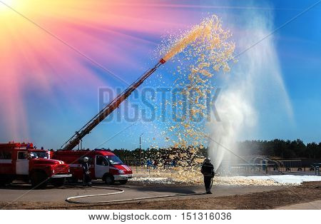 firefighter holding a fire hose with water pressure a demonstration of fire fighting equipment at sunset.