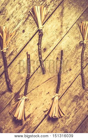 Halloween themed still life photo of home made witches broomsticks on wooden background. Witchcraft and sourcery