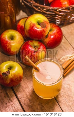 Close up of glass with fresh apple juice and cinnamon stick and ripe apples on wooden background