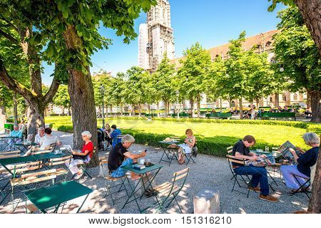 Bern, Switzerland - June 24, 2016: People sit at the outdoor cafe in the park near Munster church in the old town of Bern in Switzerland.