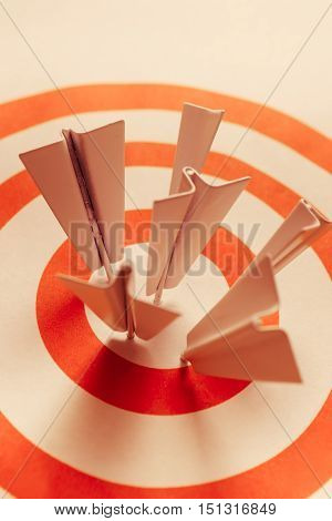 Corporate success concept with metal aeroplane darts hitting a target bullseye with spot on accuracy. Winning strategy