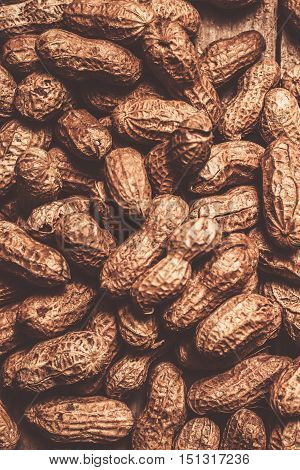 Rustic nuts still-life photo on a heap of unshelled peanuts in retro tone. Nuts background