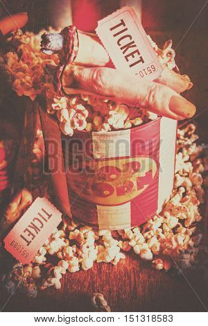 Close up of striped retro popcorn tin with hot kernals and severd fingers with horror show tickets. Spooky entertainment