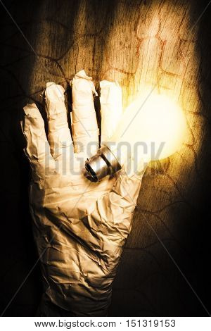 Halloween ideas concept with a shining light bulb in a crinkled mummy hand over textured wood