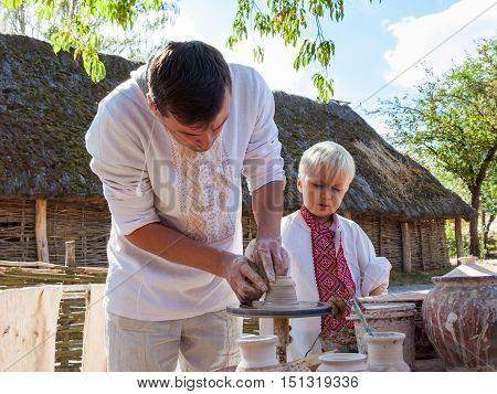 KIEV UKRAINE - SEPTEMBER 18 2016: Ukrainian man and boy making clay pot on the pottery wheel in Museum of Pirogovo village on September 18 2016. Kiev Ukraine.