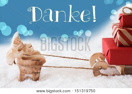 Moose Is Drawing A Sled With Red Gifts Or Presents In Snow. Christmas Card For Seasons Greetings. Light Blue Background With Bokeh Effect. German Text Danke Means Thank You