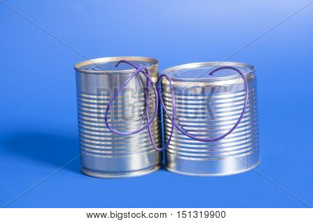 tin can phone on blue background.communication concept
