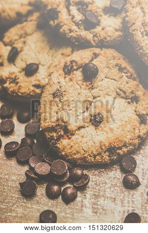 Food and dessert photography on a fresh biscuit batch of crispy chocolate chip cookies surrounded by scattered chocolate chips on rustic wooden table