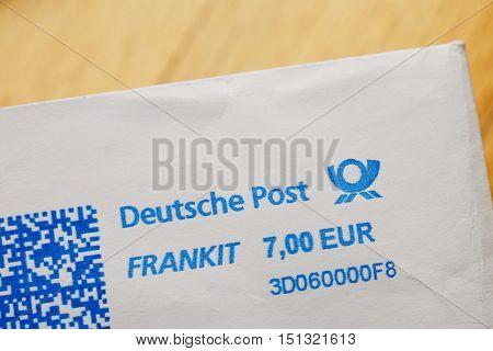 FRANKFURT GERMANY - DEC 30 2013: Deutsche Post German Post (Deutsche Post DHL) post stamp on white envelope against wooden background. Deutsche Post DHL is the world's largest courier company