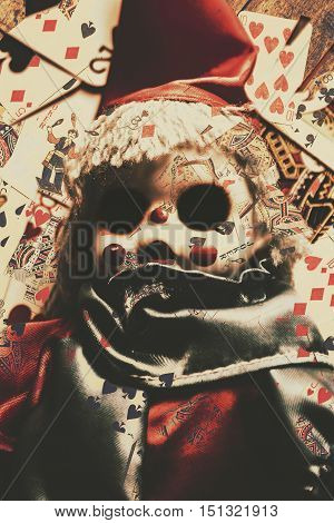 Supernatural still life photo on a jester doll under possession on playing card abstract. Hollow eyed puppet