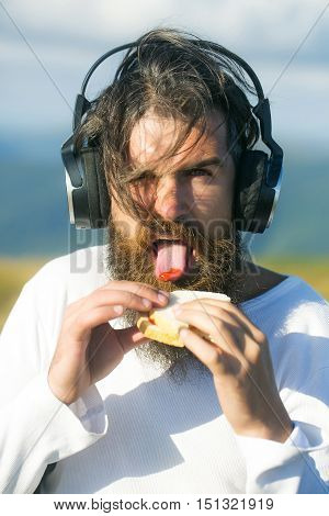 Handsome man hipster with beard and moustache with headphones eats sandwich with ketchup on sunny summer day on natural background