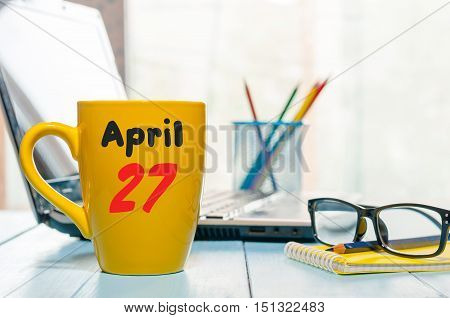 April 27th. Day 27 of month, calendar on business office background, workplace with laptop and glasses. Spring time, empty space for text.