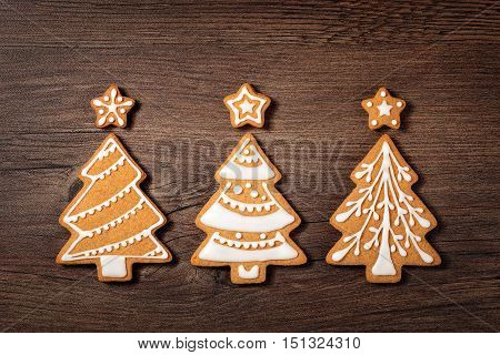 Three Christmas tree cookies with star toppers on wooden background.