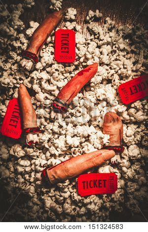 Halloween Slasher Horror Film Concept - High Angle Still Life of Severed Fingers and Red Movie Tickets Scattered on top of Popcorn