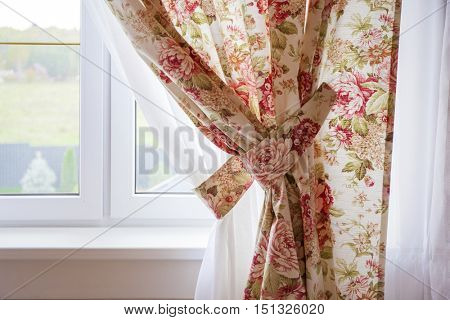 Sunlight coming through window with rose curtain