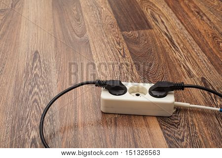 Many plugs plugged into electric power bars on floor