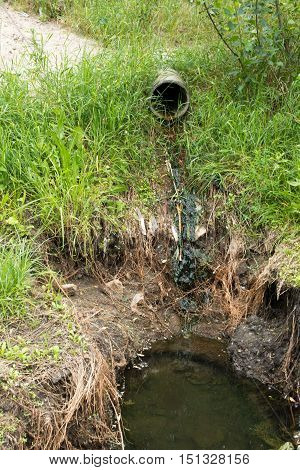 Concrete circular run-off pipe in the green grass discharging water