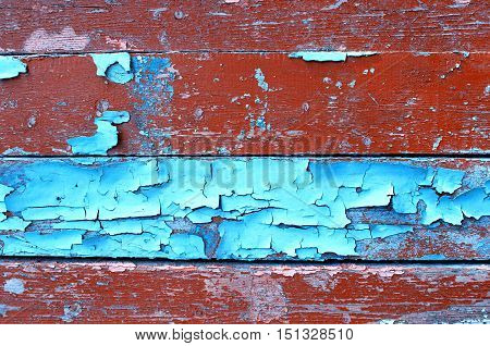 Texture background - old painted wooden surface with peeling blue and brown paint. Colorful texture wooden background