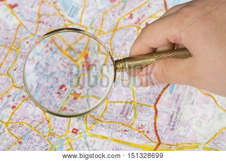 Tourism concept. Womans hand holding magnifying glass above city map.