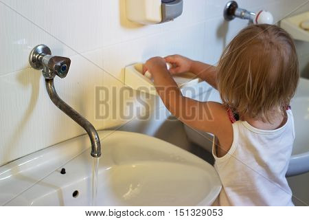 Toddler washing her hands in kindergarden before lunch