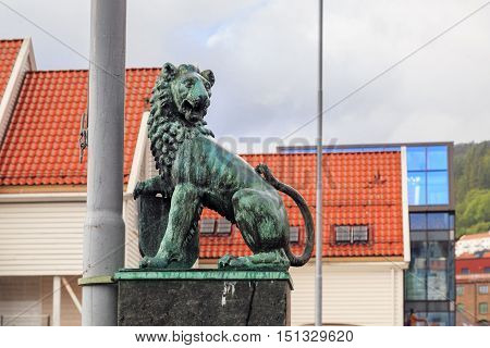 BERGEN, NORWAY - JULY 2, 2016: It is a bronze figure of a lion at the base of the flagpole in the old city haven near the fish market.