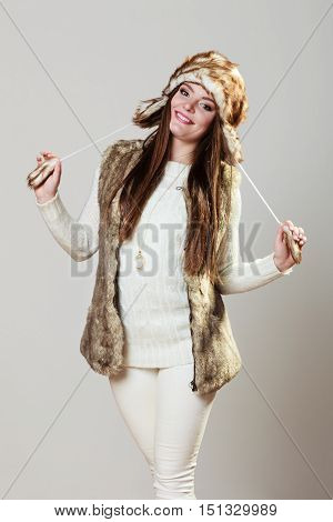 Winter cute girl fashion. Smiling woman wearing sweater fur vest and warm hat in freezing cold time.