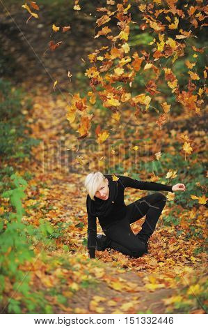 Sweet smiling blonde toying in the Park standing on the knee and throwing autumn leaves up.