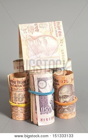 House Made Roll of Indian rupee banknotes isolated on gray