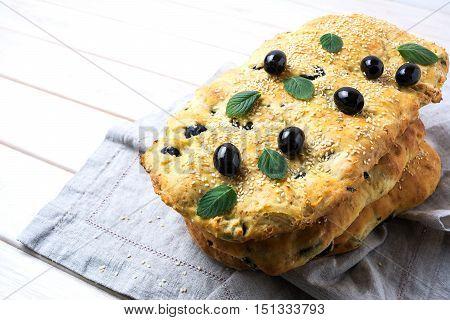 Italian bread focaccia focaccia with olive garlic and herbs. Homemade traditional Italian bread focaccia on the linen napkin.