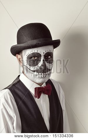 portrait of a man with a mexican calaveras makeup, wearing waistcoat, bow tie and bowler hat, against an off-white background