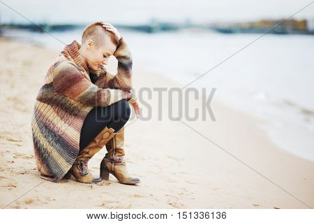 Young stylish girl with short hair in a pretty cardigan and boots is squatting on the beach in the fall and smiles. Side view.