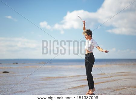 Young slim girl standing barefoot on a rock in the middle of the water on the beach and holding a bird feather
