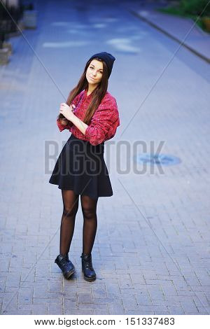 Portrait in full growth the young beautiful brunette in a short skirt a red plaid shirt and hat walking on the street in the open air