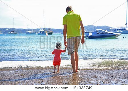 Loving Father With Daughter Walking On The Beach Carefree And Happy