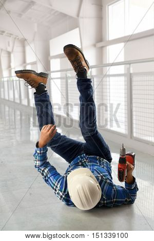 Hispanic worker falling on back inside hallway building