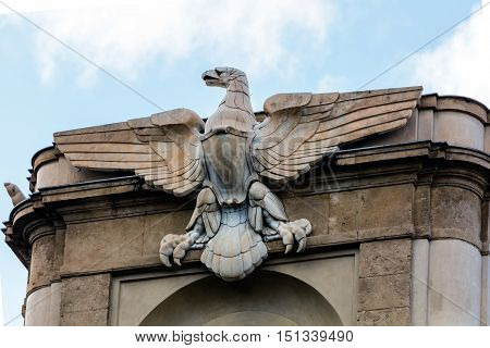 PALERMO ITALY - AUGUST 7 2016: Early 20th century Italian modernist eagle statue on top of the monumental entrance to the Via Roma built 1936 on the Piazza Giulio Cesare.