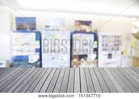 Empty top wooden table and blurred image of vending machine