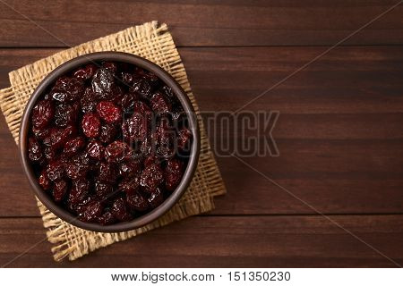 Dried cranberries in small rustic bowl photographed overhead on dark wood with natural light (Selective Focus Focus on the cranberries on the top)