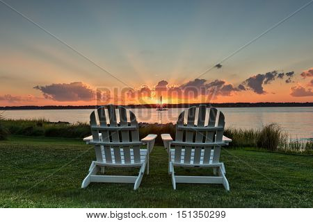 Two chairs facing Hilton Head bay viewing an iconic sunset with rays of light extending beyond the clouds.