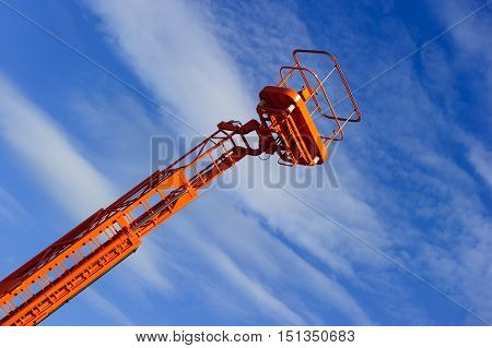 Hydraulic lift platform with bucket of orange construction vehicle, heavy industry, blue sky and white clouds on background