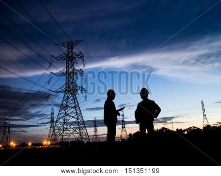Silhouette Successful male engineer standing survey work on construction over blurred high-voltage pylons and construction. examination inspection survey poster