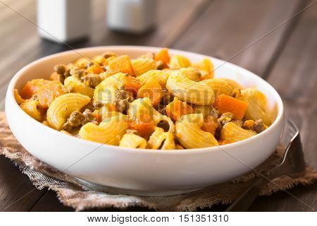 Macaroni pasta with creamy pumpkin and mincemeat sauce served in white bowl photographed with natural light (Selective Focus Focus in the middle of the dish)