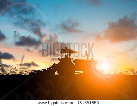 silhouette Farmer in tractor preparing land with seedbed cultivator over Blurred construction site.CSR ESG Business on industry People ScienceSigns Symbols Technology Transportation concept