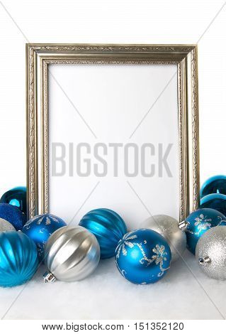 Empty Silver Frame with Silver and Blue Christmas Balls on artificial snow for a Holiday Background