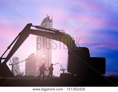 silhouette Loaders and construction worker in a building site over Blurred construction site