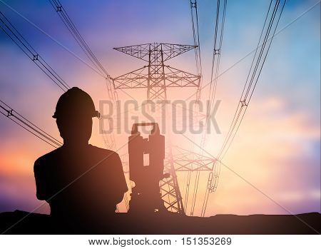 silhouette survey engineer working over Blurred high voltage transmission towers.